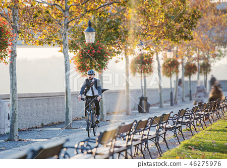 Hipster businessman commuter with bicycle traveling home from work in city. 46275976