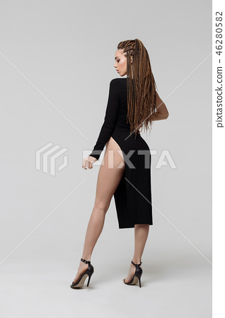 Woman with dreadlocks in elegant dress standing on light gray background 46280582