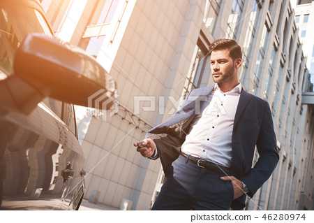 This car is perfect for me. Cheerful mature man in formalwear looking at camera and smiling while 46280974