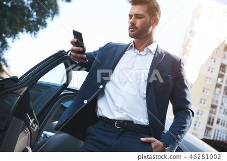 A young handsome man in a suit comes out of the car and uses smartphone 46281002