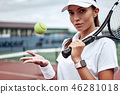 Portrait of forceful woman playing tennis in indoor court, focus on tennis racket hitting ball, copy 46281018