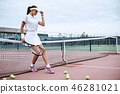 Beautiful woman in white clothing and cap with tennis racket posing at tennis net on court. Sports 46281021