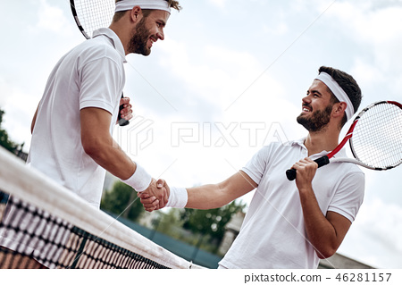 Two men, professional tennis players shake hands before and after the tennis match. One of they has 46281157