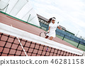 Waist up portrait of positive lady having tennis match on sunny day. She is moving near net and 46281158