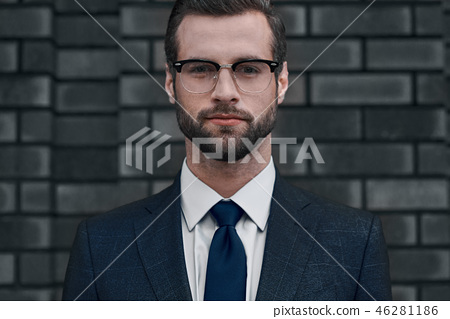 A confident view of the leader. A young businessman in glasses and with a beard looks directly at 46281186