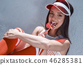 Happy beautiful young woman riding on rollers, eating candy. Summer photo. 46285381