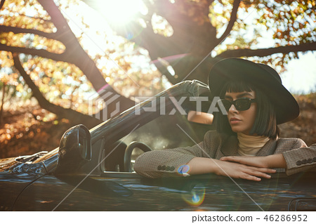 Close-up of sexy lady in sunglasses and hat is sitting in cabriolet. 46286952