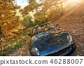 A black roofless car driving fast on the asphalt with a beautiful sunrise 46288007