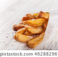 French fries in a little white paper bag. 46288296