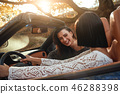 Side view of two happy women friends in cabliolet 46288398