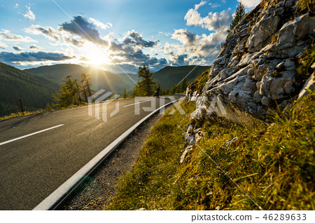 Motorcycle driver riding in Alpine highway, Nockalmstrasse, Austria, Europe. 46289633
