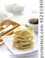 Pancakes with banana and topped with syrup. 46291940