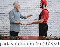 Worker Giving to Man Fixed Laptop in Workshop. 46297350