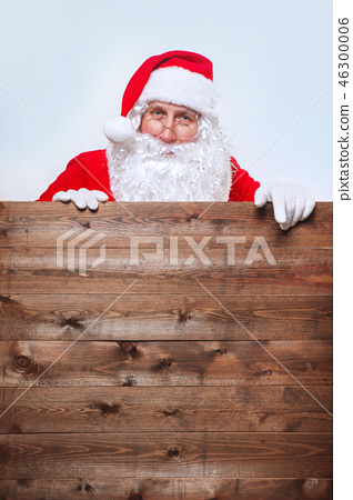 Santa Claus pointing in blank advertisement wooden banner with copy space 46300006