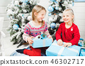 Happy little kids opening presents on Christmas eve 46302717