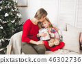 Merry Christmas and Happy Holidays. Cheerful mom and her cute daughter girl exchanging gifts 46302736