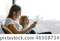 Mother and her daughter playing with toy airplane in airport terminal together 46308734
