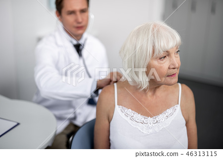 Elderly woman looking into the distance while her practitioner using stethoscope 46313115