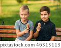 Children are sitting on the bench and eating icecream 46315113