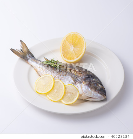 Dorada fish with lemon on a white plate. Isolated. 46328184