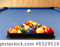 Multi colored billiard balls with numbers lie in a triangle pyramid on table. 46329516