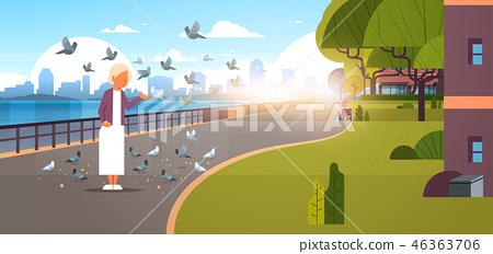 senior woman feeding flock of pigeon modern city quay urban cityscape skyscrapers background 46363706