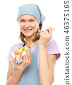Young attractive woman is eating salad using fork 46375165