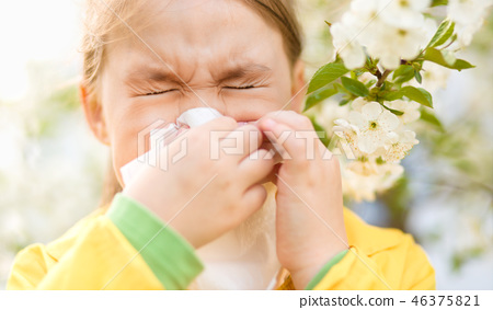 Little girl is blowing her nose 46375821