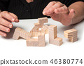 woman hand with wooden puzzle  on white table  46380774
