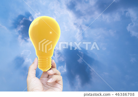Hand holding light bulb yellow pastel color 46386708