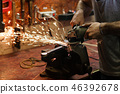 Blacksmith polishes crossguard of sword 46392678