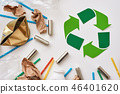 Think about ecology. Crumple paper, plastic and batteries near recycle symbol 46401620