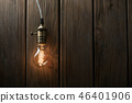 The light bulb illuminates on wooden background 46401906
