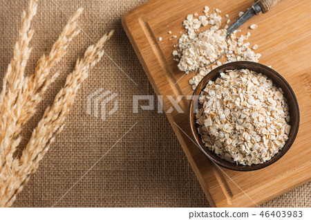 Dry oats in a wooden cup. 46403983