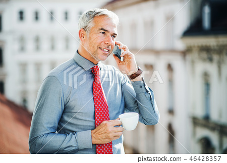 Mature businessman with smartphone standing on a terrace in city, making a phone call. 46428357