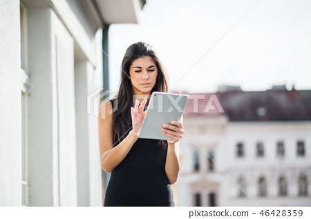 Young businesswoman with tablet standing on a terrace outside an office in city. 46428359