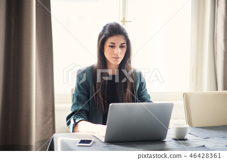Young businesswoman sitting indoors at a table, using laptop. 46428361