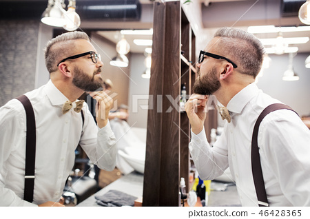 Hipster man client with glasses looking in the mirror in barber shop. 46428365