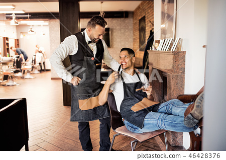 Two haidresser and hairstylist in barber shop, smoking a pipe and talking. 46428376