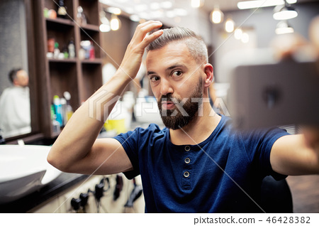 Hipster man client in barber shop, making funny faces when taking seflie. 46428382