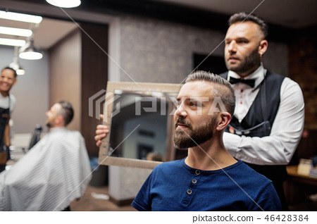Hipster man client visiting haidresser and hairstylist in barber shop. 46428384