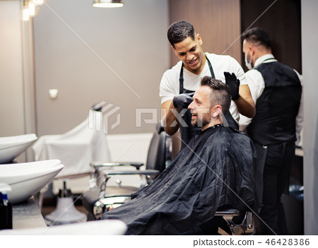 A man client visiting haidresser and hairstylist in barber shop. 46428386