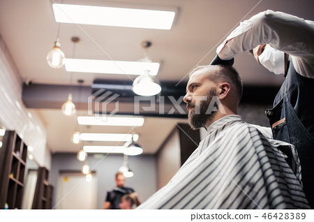 Hipster man client visiting haidresser and hairstylist in barber shop. 46428389