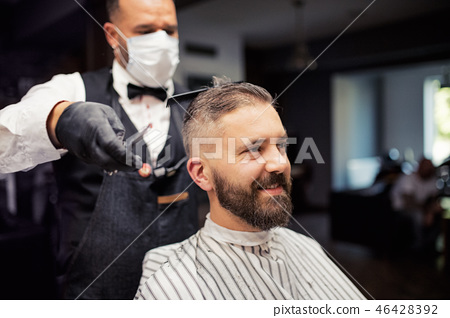 Hipster man client visiting haidresser and hairstylist in barber shop. 46428392