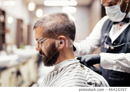 Hipster man client visiting haidresser and hairstylist in barber shop. 46428397