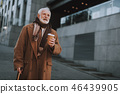 Stylish old man with hot drink walking on the street 46439905