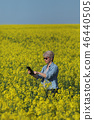 Female farmer examining rapeseed plants in field 46440505