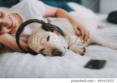 Positive attractive woman resting with her dog in bed 46442855