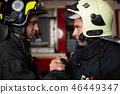 Photo of two firemen wearing helmets waving their handshake 46449347