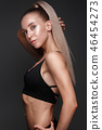 Sports girl with pumped muscles,beauty body in a tracksuit, leading a healthy lifestyle and posing 46454273